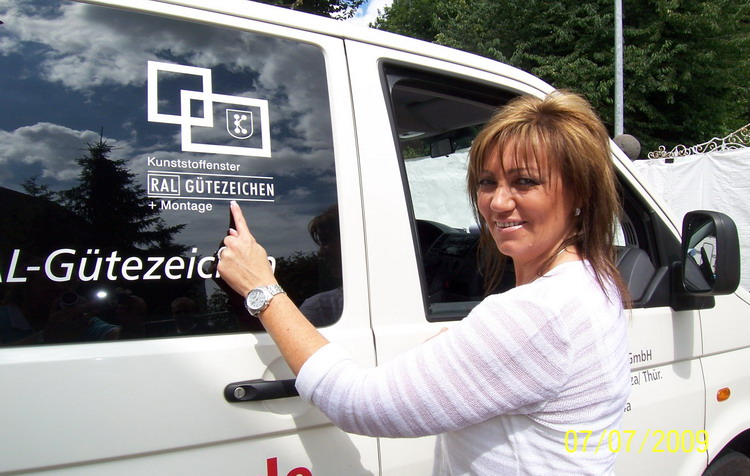 Bauherrin Anke zeigt stolz auf das RAL Gütezeichen für ihre neuen Kunststofffenster. Ganz wichtig bei einer Kaufentscheidung!