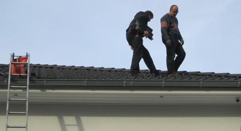 Falk Schuster und sein Mitarbeiter auf unserem Dach beim Anbringen der Schneestopnasen